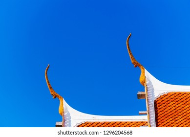 gable apex on the Buddhist temple with blue sky, temple roof is a beautifully colored tile, gable apex at the top of temple roof, thai art gable apex for worship Buddhism