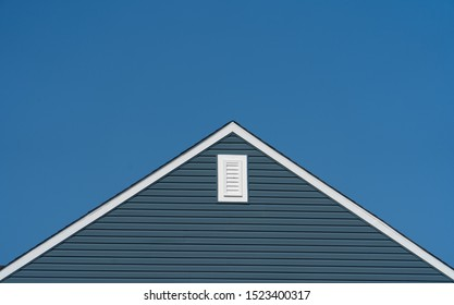 Gable with blue horizontal vinyl lap siding,  classic vertical surface mount PVC gable vent  on a pitched roof attic at an American single family home neighborhood USA