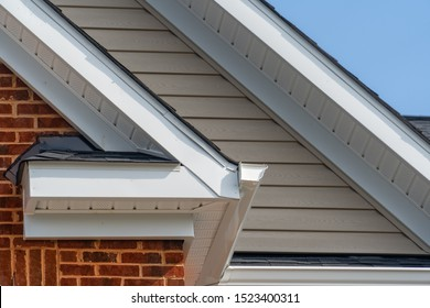 Gable with brick and vinyl siding, white frame gutter guard system, fascia, drip edge, soffit, on a pitched roof attic at a luxury American single family home neighborhood USA