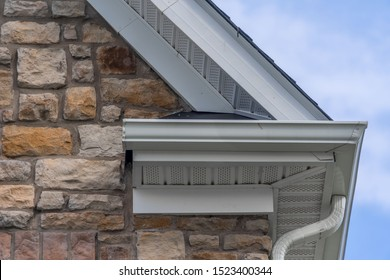 Gable with colored stone siding, white frame gutter guard system, fascia, drip edge, soffit, on a pitched roof attic at a luxury American single family home neighborhood USA