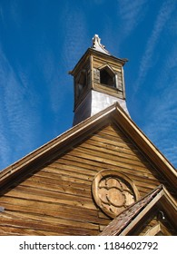 The gable front and bell tower steeple of the Methodist Church in the gold mining ghost town of Bodie, California against a blue summer sky. Built of wood in 1882, it ceased operation in 1932.