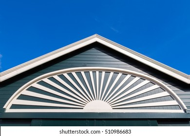 Gable of green and white building with radiating wood carving against blue sky, Netherlands.