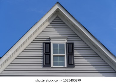 Gable with grey horizontal vinyl lap siding, double hung window with white frame, vinyl shutters on a pitched roof attic at a luxury American single family home neighborhood USA