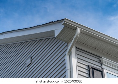 Gable with grey horizontal vinyl siding, white frame gutter guard system, fascia, drip edge, soffit, on a pitched roof attic at a luxury American single family home neighborhood USA
