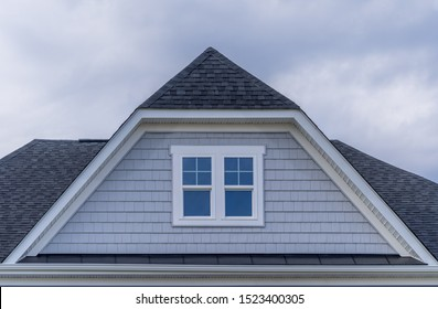 Gable with horizontal vinyl lap siding, double hung window with white frame, shingle facade on a pitched roof attic at an American luxury single family home neighborhood in the USA
