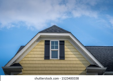 Gable with horizontal vinyl lap siding, double hung window with white frame, double vinyl shutters yellow shingle facade on a pitched roof attic at an American single family home neighborhood USA