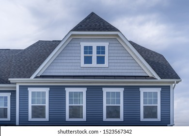 Gable with horizontal vinyl lap siding, four double hung windows with white frame, shingle facade on a pitched roof attic at an American luxury single family colonial home neighborhood in the USA