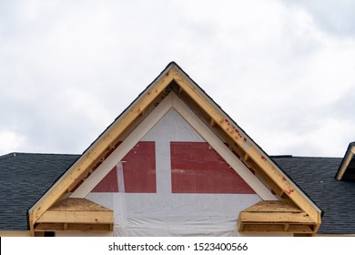 Gable with no siding just a wooden frame, house wrapping material on a pitched roof attic at a still under contruction American luxury single family home neighborhood in the USA