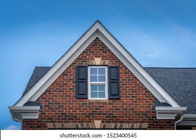 Gable with red brick facade siding, double hung window with white frame, vinyl shutters on a pitched roof attic at a luxury American single family home neighborhood USA