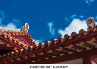 Gable roof of Shuri Castle, Traditional roof tiles with religious symbol on old castle in Okinawa, Japan, Ryukyuan cultural artifact and art with blue sky backdrop, selective focus, copy space