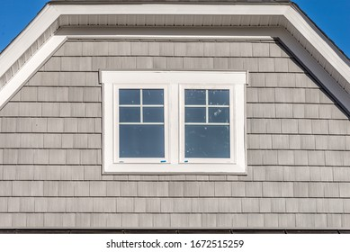 Gable with tan shingle and shake siding, double hung windows with white frame, on a dutch roof attic at an American single family home neighborhood USA