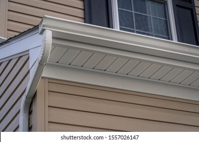 Gable with vinyl siding, white frame gutter guard system, fascia, drip edge, soffit, on a pitched roof attic at a luxury American single family home neighborhood USA
