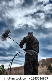GABLITZ, AUSTRIA, Nov 2017 : A chimney sweeper on the rooftop of a house checking a smoking chimney. Illustrative editorial.