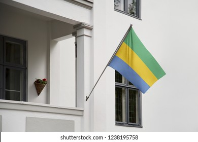 Gabon flag hanging on a pole in front of the house. National flag waving on a home displaying on a pole on a front door of a building and raised at a full staff.