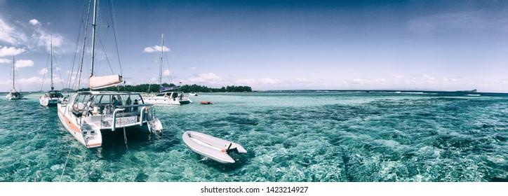 GABRIEL ISLAND, MAURITIUS - ARIL 27, 2019: Catamarans anchored near a beautiful beach. Gabriel Island is a famous tourist attraction.