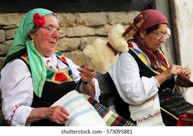 GABROVO, BULGARIA -SEP 8, 2016:  Two elderly bulgarian women in traditional dresses are engaged in needlework outdoors, Etar Ethnographic Open Air museum