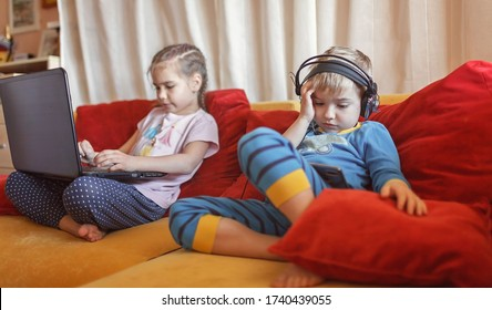 Gadget dependence, digital native generation alpha, cute kid lying on sofa and using gadgets from the early morning at home, online education and entertainment