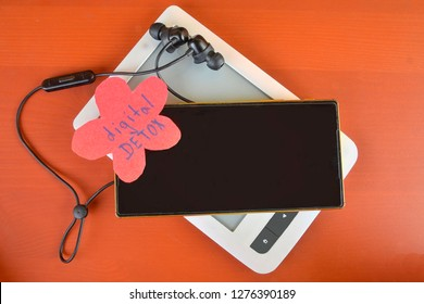 Gadget detox concept. Digital addiction concept. Mobile phone, e-book-reader and wireless headset on claret background. Modern digital technology. Copy space.
