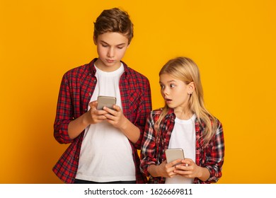 Gadget generations. Curious little sister peeking at smartphone of her elder brother, standing together over yellow background, empty space