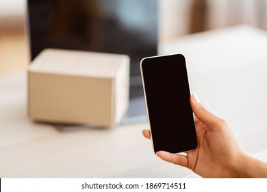 Gadget Mockup For Website Or App. Unrecognizable black lady holding mobile phone in hand, showing device with empty screen for template. Laptop with cardboard box on keyboard in blurred background