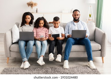 Gadgets Addiction. Portrait of African American family of four people holding and using different electronic devices while sitting on the sofa in living room at home, parents and their little children