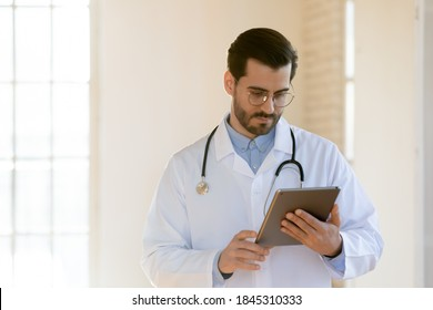 Gadgets on medical service. Pensive thoughtful millennial doctor therapist gp standing in clinic office focused on digital pad pc screen working with electronic documents, counseling patient online