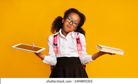Gadgets Vs Books. Afro Elementary School Girl Comparing Tablet And Book Over Yellow Background. Studio Shot