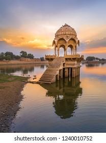 Gadi Sagar (Gadisar) Lake, Jaisalmer, Rajasthan - with ancient architecture at sunrise. A popular tourist destination in Rajasthan, India.