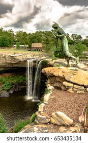 Gadsden, Alabama, USA - May 20, 2017: The  bronze statue of a young Cherokee woman named Noccalula, who legend says plunged to her death at this point with Noccalula Falls in the background.