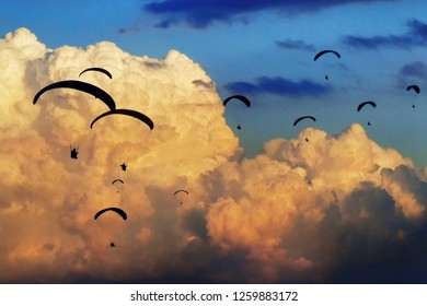 Gaggle of paragliders fly with giant clouds on the background. Paragliding competition