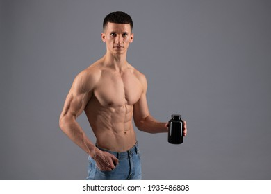 Gain mass. Muscular guy hold bottle of dietary supplemets. Sports nutrition supplements. Mass-gaining diet. Have your protein on the go, copy space.