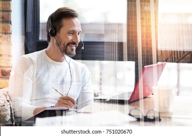 Gaining new knowledge. Pleasant cheerful man watching a video stream of a webinar and making notes while wearing a headset with a microphone