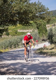 GAIOLE IN CHIANTI, ITALY - 5 OCT. 2014: Unidentified participants of L'Eroica, a historic cycling event for owners of vintage bicycles and apparel who ride through Tuscany on white gravel roads