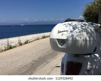 Gaios Paxos, Greece: 7th of July 2018: White Vespa motorcycle parked on the street in the city of Gaios on Paxos Island in Greece. In the background beautiful Ionian sea. Photographed with mobile.
