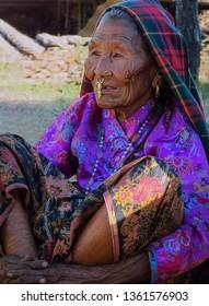 Gairi Pangma, Sankhuwasabha District, Nepal - 11/18/2017: Beautiful old Rai woman with wrinkled face wearing a traditional scorpion nose ornament sitting outside on the ground