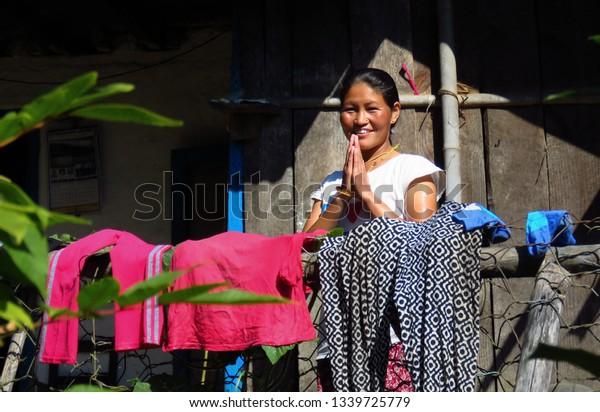 Gairi Pangma, Sankhuwasabha District, Nepal - 11/19/2017: Namaste! Smiling Nepalese woman says hello with the palms together like a prayer.