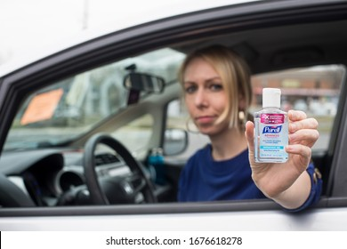 Gaithersburg, Maryland / USA - March 18, 2020: A young woman shows off her bottle of Purell hand sanitizer, a disinfectant that is out of stock in most stores as a result of the COVID 19 pandemic.