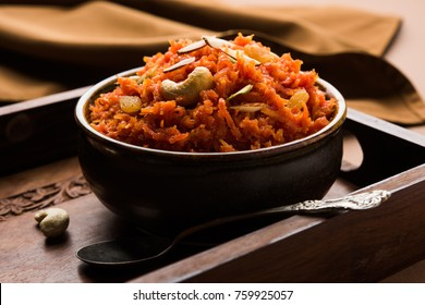 Gajar ka halwa is a carrot-based sweet dessert pudding from India. Garnished with Cashew/almond nuts and Served in a bowl over colourful/wood background