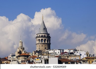 Galata Tower and its surroundings with clouds in the background.