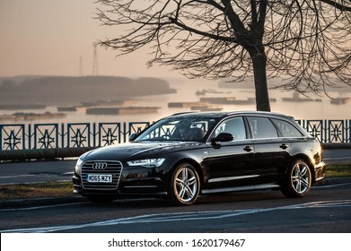 Galati, Romania - January 13, 2020: Black Audi A6 C8 facelift front and view with a beautiful sunset landscape in background