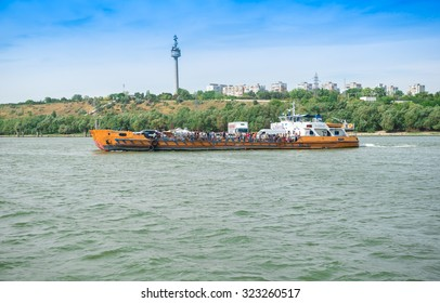 GALATI, ROMANIA - SEPTEMBER 06, 2015: Ferry boat filled with people and cars crossing Danube river from town Galati to town Braila with the television tower from Galati in the background