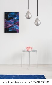 Galaxy graphic on the white wall of spacious interior with stylish sliver lamps blue carpet and metal coffee table with pastel pink telephone