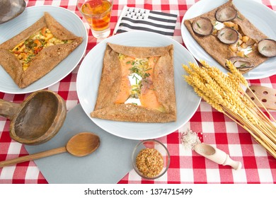 Galette complete. Traditional French buckwheat crepe. Breton speciality pancake buckwheat crepe, with egg, cheese, ham, andouille, salmon, potatoes, at served with a red and white checkered tablecloth