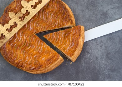 Galette des rois, french kingcake with a golden crown on slate background