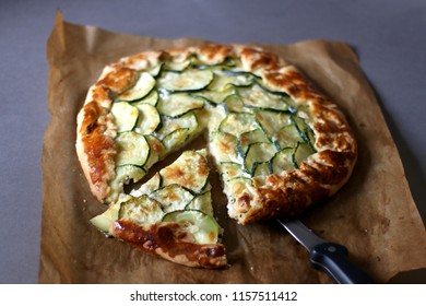 Galette made with courgette and cheese (ricotta, mozzarella, parmesan). Top view, selective focus.