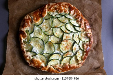 Galette made with courgette and cheese ricotta, mozzarella, parmesan. Top view, selective focus.