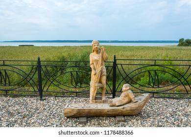 Galich, Kostroma Region, Russia - 11.09.2018: Wooden sculpture of a woman-fisherman on the embankment of Galichsky Lake September 11, 2018, Galich, Kostroma Region, Russia.