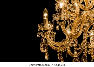 Gallant chandelier with light candles and dark side background. Luxury candelabra hanging on ceiling with lots of little gems. Black background and copyspace on the left side