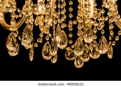 Gallant chandelier with light candles and dark background . Luxury candelabra hanging on ceiling with lots of little gems