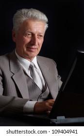 Gallant elderly man in suit on black background